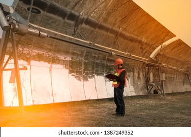 The worker in orange uniform and helmet checks Solar Parabolic Troughs.
