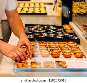 Worker organising rows of freshly cooked egg tart, traditional portuguese dessert, pastel de nata, custard tarts.