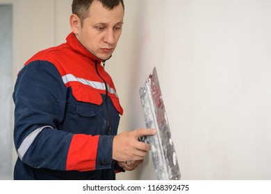Worker in overalls plastering a wall with finishing putty using a putty knife. Repair work and construction concept