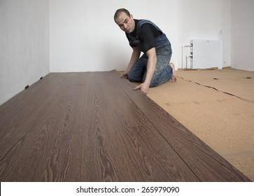 Worker in overalls puts laminate brown indoors