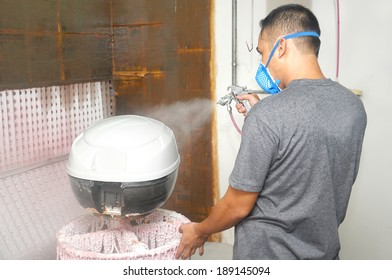 Worker painter wearing a protective mask painting a white color undercoat