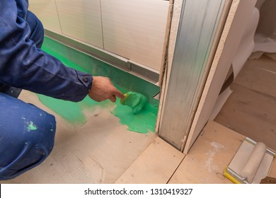 Worker is painting by brush with green colored waterproof finish material the bathroom floor in apartment is inder construction, remodeling, renovation, overhaul, extension, restoration and