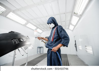 worker painting a car black blank parts in special garage, wearing costume and protective gear