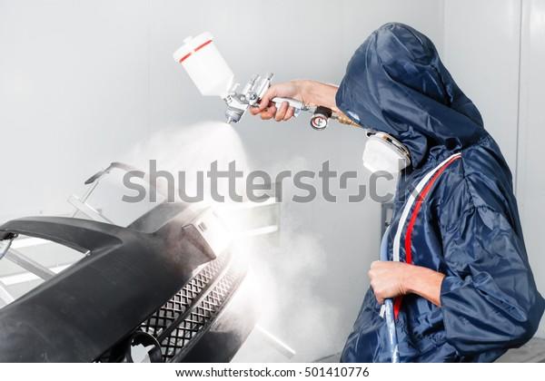 Arbeiter, der in einer Sondergarage schwarze Autoleerteile anstrich, Tracht und Schutzausrüstung trägt