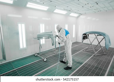 Worker painting a car parts in a paint booth,