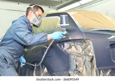 Worker painting a gray car in a paint chamber.