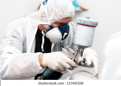 worker painting a grey car wearing a special costume