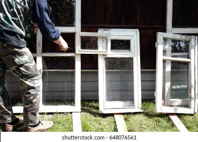 Worker painting old wooden windows with paint brush, standing outdoor