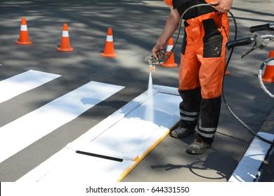 Worker is painting a pedestrian crosswalk.