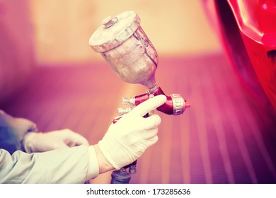 Worker painting a red car in painting booth using professional tools and spray gun