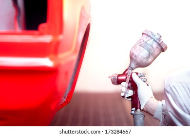 worker painting a red car or element in a special garage, wearing a grey costume