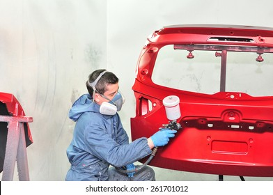 Worker painting red car part.