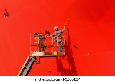 Worker painting ship hull on sherry picker using paint roller