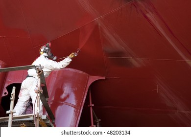 worker painting ship hull using airbrush red paint