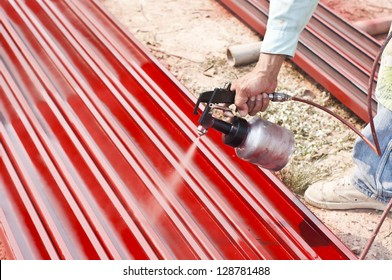 Worker painting steel bars using airbrush.