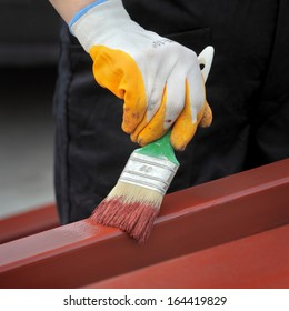 Worker painting  steel tube with paint brush selective focus on hand