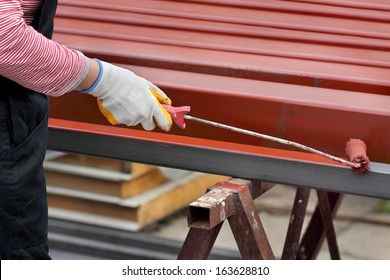 Worker painting  steel tube with paintroller selective focus on hand