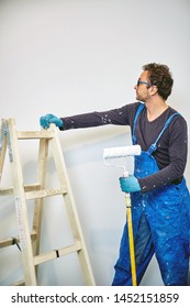 Worker painting walls inside the house - renovation fixes.