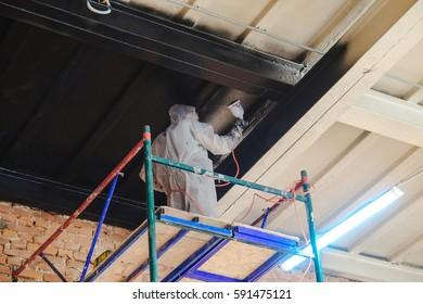 worker paints by spray gun