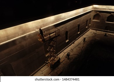 Worker Paints a Primer Wall with a Paint Spray Gun at Night