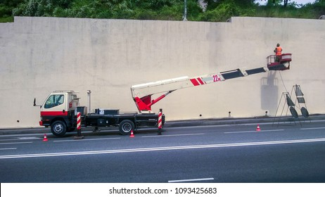 Worker paints the walls on the street