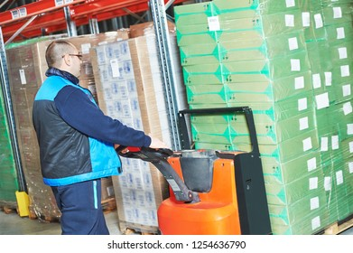 Worker with pallet truck loading cardboxes