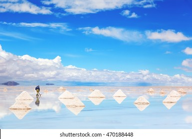 Worker performing harvesting salt on the salt lake Salar de Uyuni, Bolivia (focus on worker)