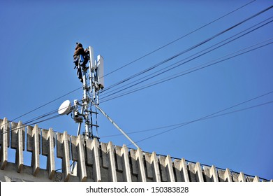 A worker performing maintenance to a GSM communication antenna
