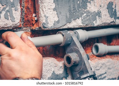 The worker performs the connections of polypropylene plumbing pipes