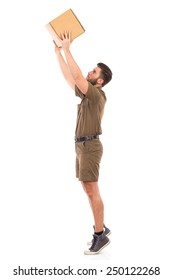 Worker picking up a package. Delivery man in khaki uniform picking up a carton box. Full length studio shot isolated on white.
