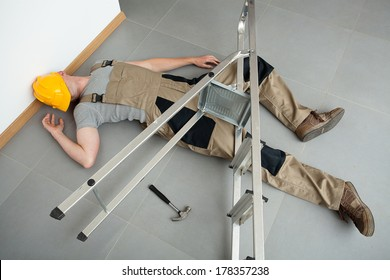 A worker pinched by a ladder which has fallen on him