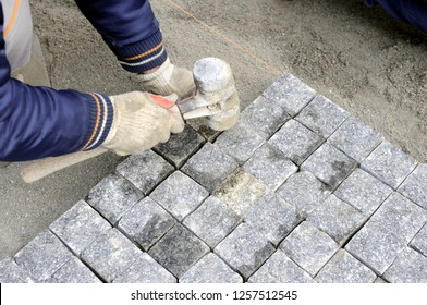 A worker places cobblestones patern on the street with rubber hammer manualy