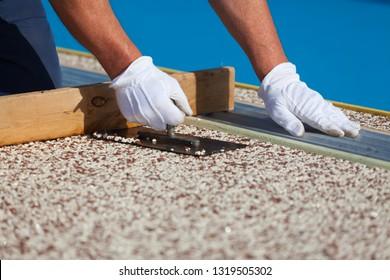 Der Arbeiter legt einen Steinteppich mit Harz. (SCHLAFER DOF).
