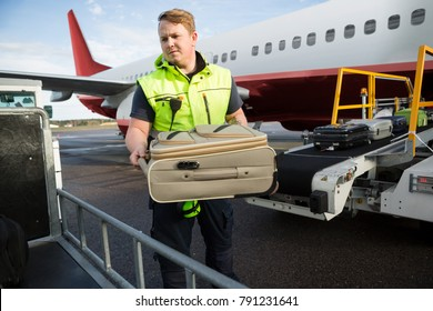 Worker Placing Luggage In Trailer Against Airplane