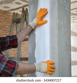 Worker placing reinforcing corner mesh to pillar over styrofoam insulation