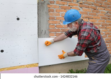 Worker placing styrofoam, polystyrene  insulation to brick wall, house renovation