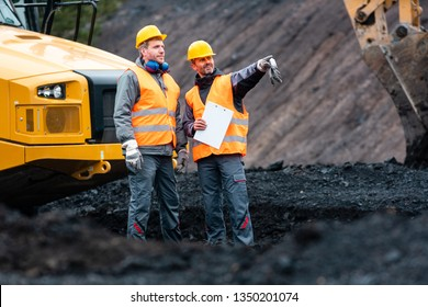 Worker with a plan and a clipboard discussing super important things in quarry