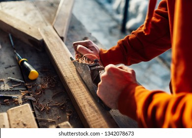 a worker planes a wooden bar with a plane, on the table in sawdust the floor is sunlight.