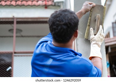 A worker is plastering cement on the wall in the construction work