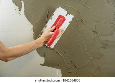 A worker plasters the wall with a spatula and applies a cement mix solution. The repairman lays the plaster on the drywall. Handyman repairs home. Laborer restore dwelling. Specialist covers up cracks