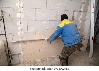 A worker plasters the walls in the room. Building a house