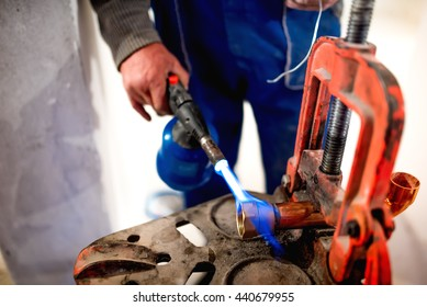 worker, plumber using blowtorch for soldering copper fittings