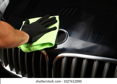The worker polishes the car with special rag. Close up.