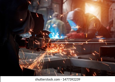 Worker polishes a metal surface with a grinder
