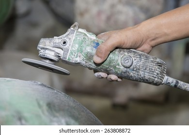 worker polishing and cutting Fiberglass with angle grinder, power tool used for cutting, grinding and polishing