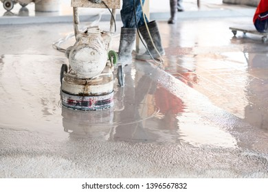 Worker polishing stone concrete with machine