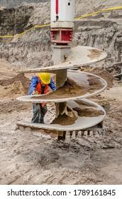 Arbeitskraft, die ein Bohrwerkzeug einrichtet, um einen Erdtunnel zu ertragen  Nahaufnahme einer Bohrspindel oder einer Bohrmaschine, die in Baustellen verwendet wird