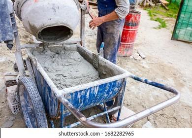 Die Arbeiter gießen Beton vom Zementmischer in den Rollkarren.