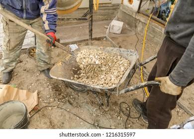 Worker pours gravel at a construction site