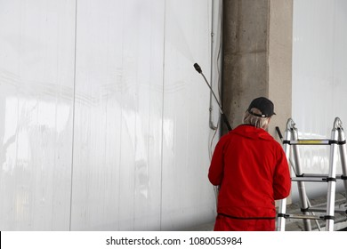 Worker power washing wall